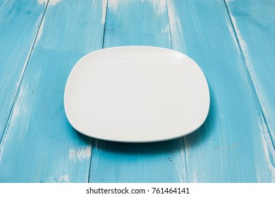 White plate on blue wooden table with perspective side view