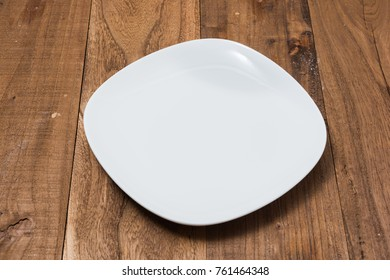 White Plate on brown wooden table background side view