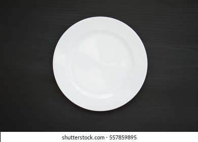 White plate on a wooden floor after dark.