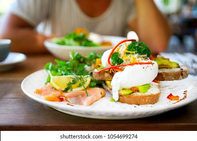 A white plate on a wooden table in a cafe in Bali in Ubud, Canggu. Breakfast in the restaurant with eggs poached, salmon, avocado, beans, salad, red pepper, mushrooms. Blurred background with man