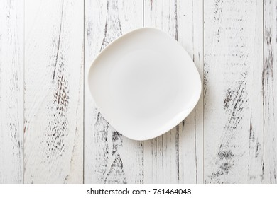 White Plate on white wooden table background