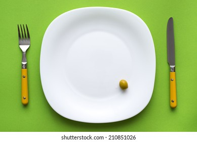 white plate with one olive and cutlery on green tablecloth