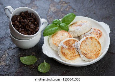 White plate with pan fried curd pancakes or syrniki and coffee beans, studio shot, selective focus