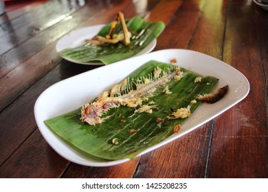 The white plate, primed with green banana leaves, placed on a brown wooden table in the dish with a fishbone frame placed.