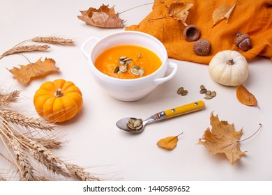 White plate with pumpkin soup and autumn leaves on a wooden table