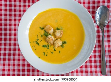 white plate with pumpkin soup and spoon on red and white checkered tablecloth top view