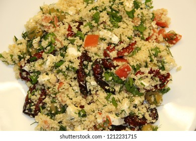 White plate with salad of cuscus, dry and fresh tomatoes, feta cheese, olives, dill, parsley, oleve oil, garlic