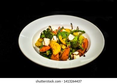a white plate setup showing a delicious home made salad consisting of a variety of  vegetables like capsicums, cottage cheese, broccoli, tomatoes, baby corns etc served with a sauce dressing