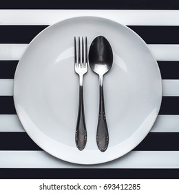 A white plate with silver fork and spoon on it, striped background