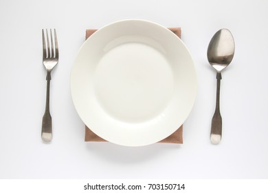 A white plate with silver fork and spoon isolated on white background.