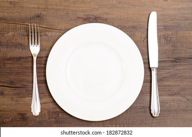 White plate with silver knife and fork on a wooden board