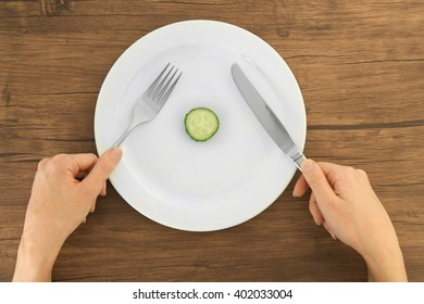 White plate with a slice of cucumber on wooden table