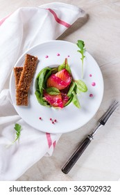 White plate with Sliced salmon filet, salted with beetroot juice, served with whole wheat toasts, salad leaves and beetroot sauce over white marble surface with white textile and fork. Top view