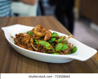 White plate of Stir-Fried Twisted Cluster Bean or Bitter Bean or Stink Bean with Shrimps paste. Selective focus.