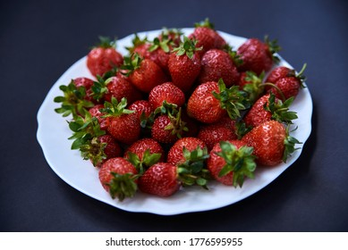 White plate with strawberries on table. Close-up picture of red berries on black background. Healthy nutrition in summertime. Juicy, rich in vitamins vegetarian food. Fruit crop.
