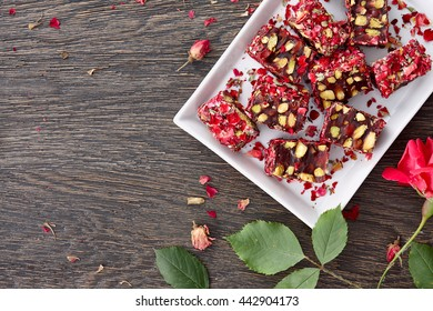 A white plate with traditional turkish delight decorated with rose petals on a dark wooden background, top view.