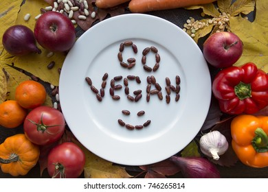 White plate with various vegetables and go vegan text top view