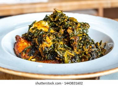 A white plate of vegetable soup on a white background. Nigerian food: A bowl of Efo Riro soup
