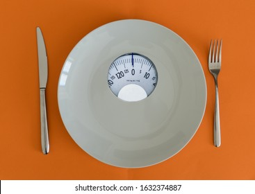 White plate with weight scale. Anorexia and eating disorder concept.