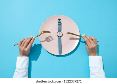 White plate whatch with blue band shows six o'clock served knife and fork in a girl's hands on a blue background, place for text. Time to eat and diet concept. Top view.