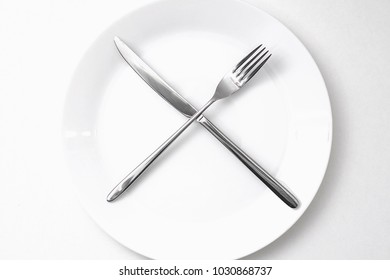 white plate without food with a fork and knife