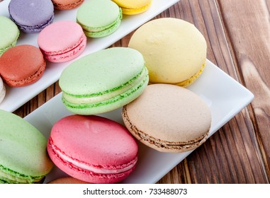 White plates with color macaroons. Macaroons on a wood texture. Sweets macaroons. French desert - macaroons.