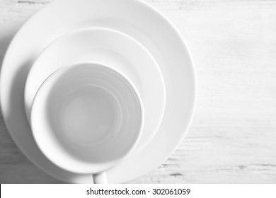 White plates and cups on a light wooden background