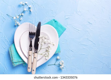 White plates in form of hearts, napkin, knife and fork and  fresh white gypsofila  flowers on blue textured background. Top view. Flat lay.