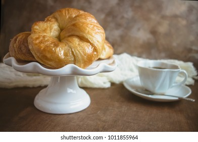 A white platter of croissants on wooden table with a cup of coffee.
