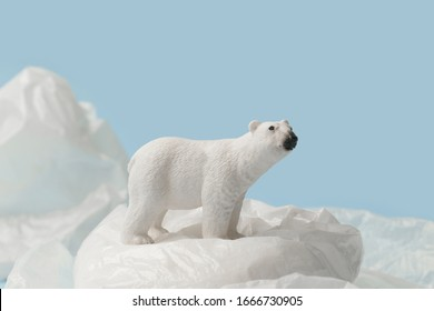 White polar bear on plastic bag on blue background, plastic pollution and climate change concept