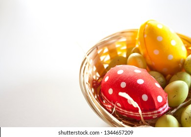White polka dot yellow and red easter eggs and small green eggs in a wicker basket