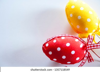 White polka dots easter eggs. Red and yellow eggs as wallpaper. Space for text. Easter mood.