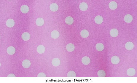 White polka dots pattern on pink background, Polka dot fabric background and texture.