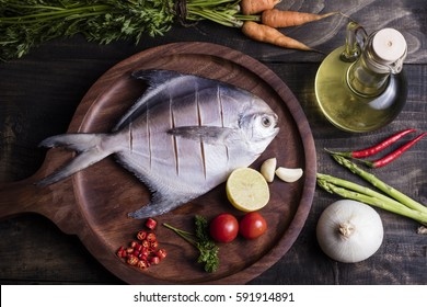 White pomfret fish places on a wooden board.