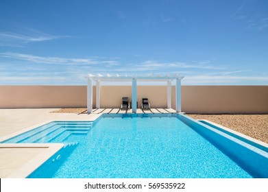 White poolside pergola, gazebo next to an infinity pool swimming pool with steps and blue tiles.