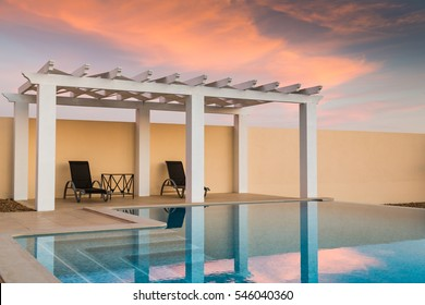 White poolside pergola, gazebo providing shade on a terrace patio area next to an infinity swimming pool at dusk as the sunset turns the sky pink orange.