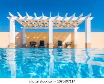 White poolside pergola, gazebo taken from the swimming pool. The reflection of the pergola can be seen in the blue rippling water