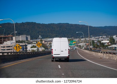 White popular compact comfortable commercial useful economical small business or cargo delivery mini van running on the wide highway in industrial area of urban city to point of destination