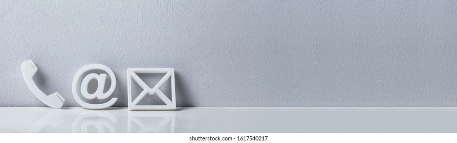 White Popular Contact Web Icons On Desk Over The Reflective Desk Against Gray Wall - Shutterstock ID 1617540217
