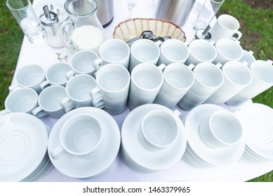 Lot of white porcelain coffee cups in the table in outdoors summ