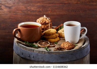 White porcelain mug of tea and sweet cookies on wooden background, top view, selective focus