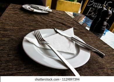 White porcelain plate, knife, fork, paper napkin, saltpeter set on the street restaurant table with a brown tablecloth