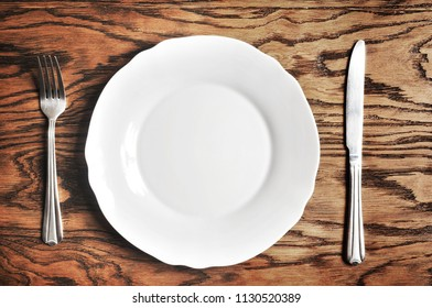 White porcelain plate, silver fork and knife on the dark wooden background