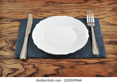 White porcelain plate, silver fork and knife on the blue board on the dark wooden background