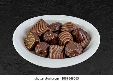 Soucoupe de porcelaine blanche, remplie de divers chocolats. Isolé sur fond structuré sombre.
