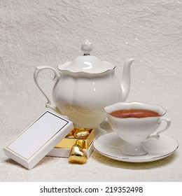 White porcelain teapot and cup of tea and a box of gold candies
