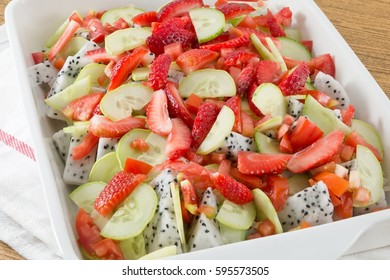 White Porcelain Tray of Fruits Salad, Strawberries and Dragon Fruit with Cucumbers and Tomatoes.