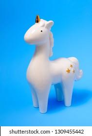 White porcelain unicorn figurine on blue pastel background. White unicorn. Home decoration unicorn.  Unicorn photos.