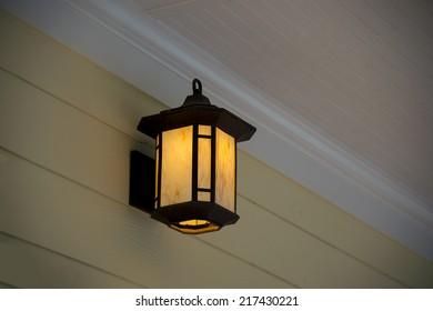 A white porch light against a brown vinyl siding