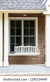 White porch swing in front of window and between columns of a brown shingled house - vertical